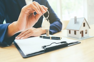 man giving keys after using a Real Estate & Land Use attorney