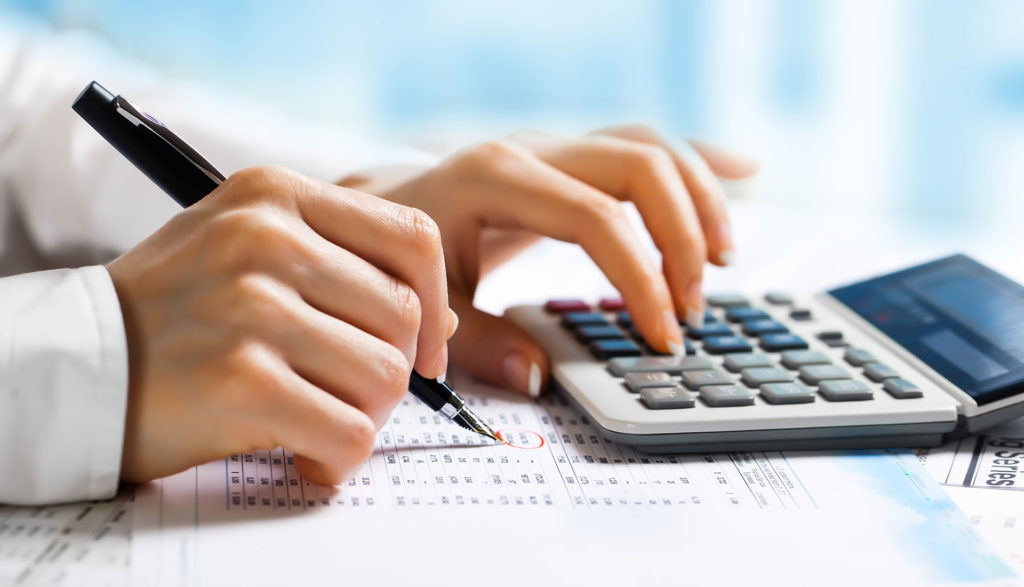 business tax and finance attorney at OFP Law using a calculator
