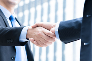 a handshake between an elder man and an estate planning lawyer as they meet to discuss wills and estates