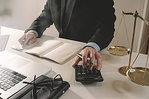 a trusts & estates attorney using a calculator to calculate finances