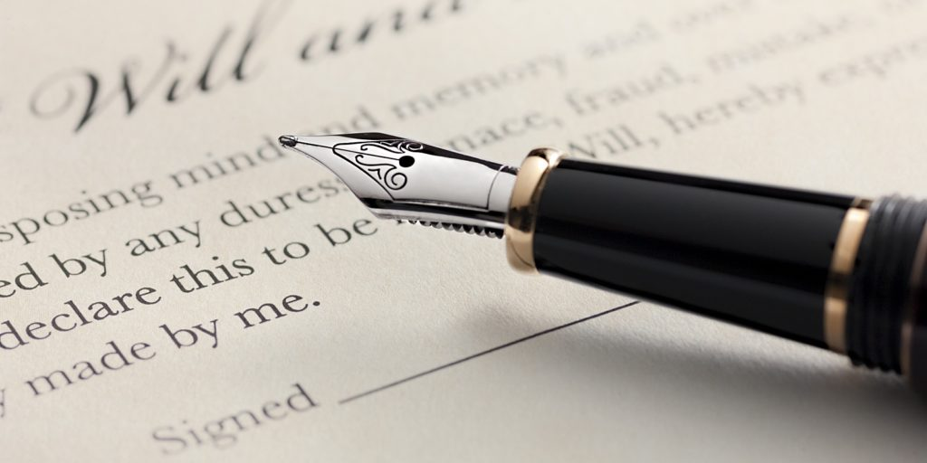 a will that is being signed by an individual during an estate planning meeting with trust & estate attorneys