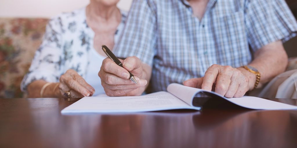 an elderly couple signing will and estate documents during their estate planning meeting
