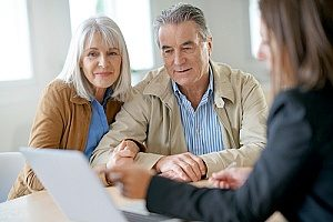 an elderly couple working with an estate planning lawyer to come up with estate plans in case they were to pass away