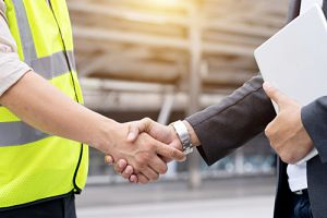 A construction attorney from OFP Law shaking hands with a contractor