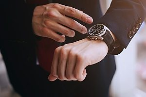 a business man using a watch to set a timetable for his business succession plan