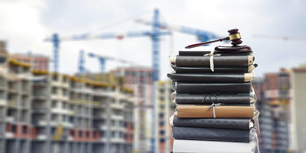 a stack of construction law books in front of a construction zone