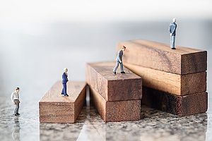 small figurines climbing steps to represent business succession planning