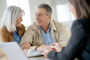 A cheerful senior couple looking over documents with an estate planning attorney