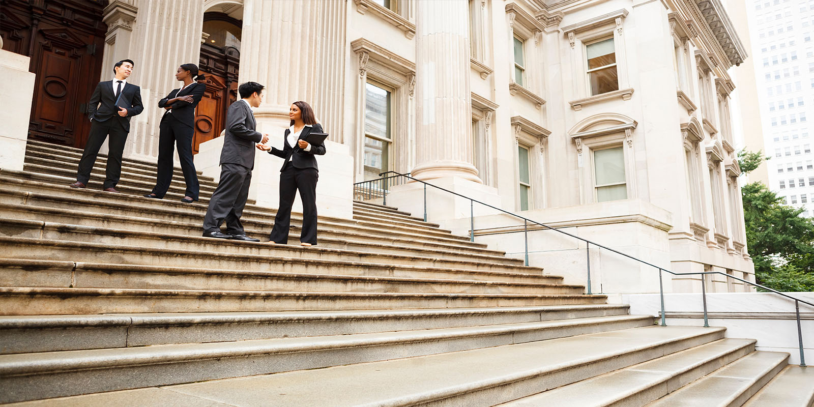 Four well dressed professionals in discussion on the exterior steps of a building