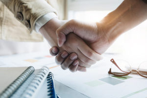 closeup of two business people shaking hands and agreeing to a merger